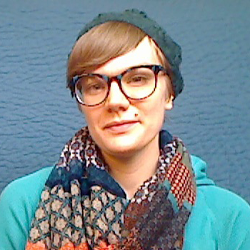 Sarah Schieffer Riehl, a white woman in her 30s with big glasses and short fair hair
